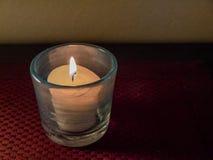 Zaświecająca wotywna świeczka w szklanym właścicielu Zdjęcia Stock