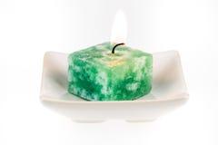 Zaświecająca zielona świeczka na talerzu Obrazy Stock
