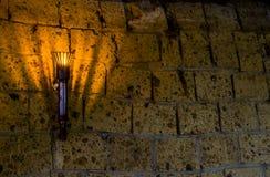 Zaświecający średniowieczny grodowy pochodni obwieszenie na kamiennej ścianie, roczników przedmiotach i tle, obrazy royalty free