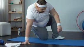 Zażywny mężczyzna obsiadanie na macie dla ćwiczyć, trudzący się oddychanie, otyłość problemy zbiory