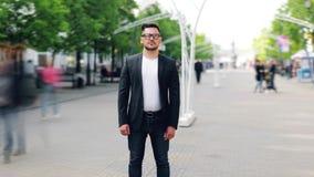 Za czasu upływie młoda biznesmen pozycja w ruchliwie miasto ulicie samotnie zdjęcie wideo