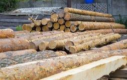zaagmolen De stapel van het pakhuishout Logboeken van pijnboom voor het zagen van het timmerhout van de stralenraad stock afbeeldingen