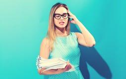 Zaakcentowana biurowa kobieta z stertą dokumenty Zdjęcia Stock