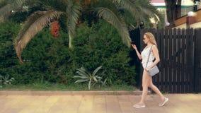 Zaakcentowana kobieta opowiada na telefonie na ulicie, mieć nerwową rozmowę, czujący ból i migrenę steadicam zdjęcie wideo