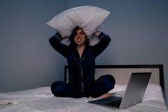 Zaakcentowana kobieta w łóżkowym mieniu poduszka na jej ręce obrazy stock