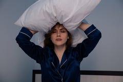 Zaakcentowana kobieta w łóżkowym mieniu poduszka na jej ręce zdjęcie royalty free