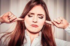 Zaakcentowana kobieta z zamkniętymi oczami stawiającymi dotyka w ucho, fotografia stock