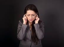 Zaakcentowana smutna biznesowa kobieta w popielatym kostiumu zamykał jej ucho żebro zdjęcia stock