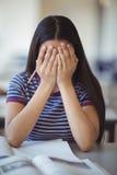 Zaakcentowana uczennica robi zakrywający jej twarz w sala lekcyjnej Obrazy Stock