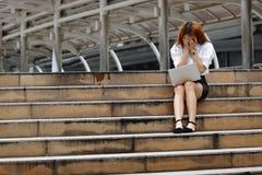 Zaakcentowana wzburzona młoda Azjatycka biznesowa kobieta z rękami na twarzy uczuciu rozczarowywającym lub męczącym z pracą zdjęcia royalty free
