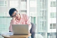 Zaakcentowany Azjatycki biznesmen używa laptop w żywym pokoju obrazy stock