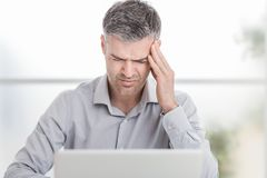 Zaakcentowany biznesmen pracuje przy biurowym biurkiem i ma migrenę, dotyka jego świątynie obrazy stock