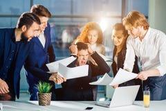 Zaakcentowany biznesmen w biurowym wrzasku, spęczenie z pracownikami pyta dla uwagi obrazy royalty free