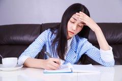 Zaakcentowany biznesowej kobiety obsiadanie przy jej biurkiem i pisze notatce dalej obrazy royalty free