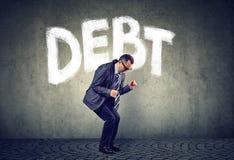 Zaakcentowany biznesowy mężczyzna pod długu naciska pieniężnym ciężarem obraz stock