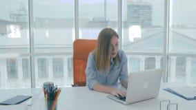Zaakcentowany bizneswoman pisać na maszynie na jej laptopie zbiory wideo