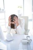 Zaakcentowany bizneswoman pracuje przy jej biurkiem Obrazy Royalty Free