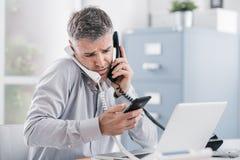 Zaakcentowany desperacki biznesmen pracuje w jego biurze i ma wielokrotność wezwania, trzyma dwa handsets i telefon komórkowego, fotografia stock