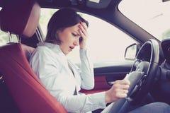 Zaakcentowany desperacki młoda kobieta kierowca siedzi wśrodku jej samochodu z dokumentami zdjęcie royalty free