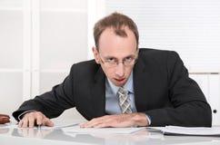 Zaakcentowany i gniewny biznesmen przy biurkiem. zdjęcia royalty free