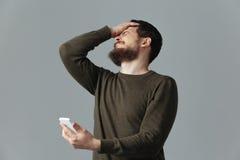 Zaakcentowany mężczyzna mienia smartphone zdjęcie royalty free