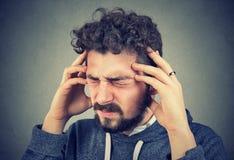 Zaakcentowany młody człowiek ma migrenę obraz stock