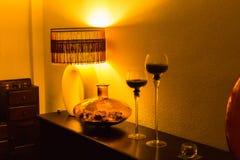Zaal binnenland met houten ladenkast, uitstekende lamp, vaas en kandelaars tegen de lichte muren in nachtverlichting Binnenlands stock afbeelding