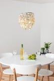 Zaal met decoratieve kroonluchter en witte rondetafel Stock Foto