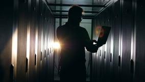 Zaal met servers en een silhouet van een mannelijke computeringenieur stock video