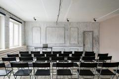 Zaal voor lezing met heel wat donkere stoelen De muren zijn wit, zolderbinnenland Op het recht is er een deur op Royalty-vrije Stock Afbeeldingen