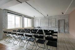Zaal voor lezing met heel wat donkere stoelen De muren zijn wit, zolderbinnenland Op het recht is er een deur op royalty-vrije stock afbeelding