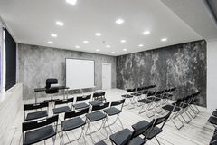 Zaal voor lezing met heel wat donkere stoelen De muren zijn wit, zolderbinnenland Op het recht is er een deur op Stock Afbeelding