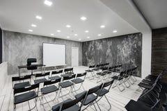 Zaal voor lezing met heel wat donkere stoelen De muren zijn wit, zolderbinnenland Op het recht is er een deur op Royalty-vrije Stock Fotografie