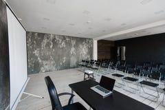 Zaal voor lezing met heel wat donkere stoelen De muren zijn wit, zolderbinnenland Op het recht is er een deur op Royalty-vrije Stock Foto's