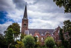 ZAANDAM NEDERLÄNDERNA - JUNI 13, 2016: Allmänna landskapsikter i traditionell kyrklig arkitektur av den Zaan regionen på skymning Arkivfoto