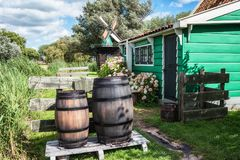 Rain barrels in front of a characteristic small green house on t. Zaandam, The Netherlands, August 4, 2017: Rain barrels in front of a characteristic small green Stock Photography