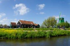 Zaanse Schans, Países Baixos - 5 de maio de 2015: Moinhos de vento da visita do turista e casas rurais em Zaanse Schans Fotos de Stock Royalty Free