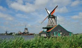 The Zaanse Schans. The Zaanse Schans is a small village on the banks of the Zaan river, complete with tidy green houses, real working windmills, and small royalty free stock images