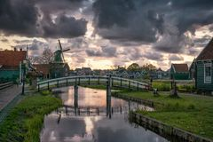 Zaanse Schans windmill landscape in the Netherlands, sunset cloudy sky. Bridge over canal Royalty Free Stock Photo