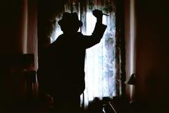 Zabójca sylwetka w ciemnym pokoju Obrazy Royalty Free