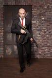 Zabójca trzyma maszynowego pistolet w kostiumu i czerwonym krawacie Fotografia Stock