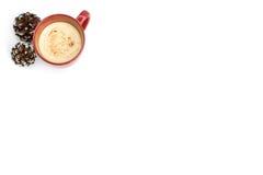 Zabaione della cannella in tazza rossa con i pinecones nevosi fotografia stock