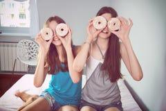 Zabarwiać wizerunku dwa nastoletnie dziewczyny ma zabawę z donuts zdjęcie stock