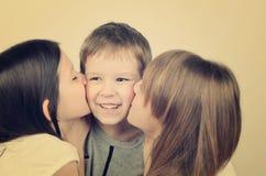Zabarwiający wizerunek dwa wiek dojrzewania dziewczyny całuje małej roześmianej chłopiec Fotografia Royalty Free