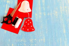 Zabawa czuł Bożenarodzeniowego dzwonu ornamentu, białych i czarnych nici, nożyce, papieru wzór, filc prześcieradła na błękitnym d Zdjęcia Stock