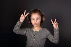 Zabawa dzieciaka grimacing dziewczyna słucha muzykę w bezprzewodowym hełmofonie Obrazy Royalty Free