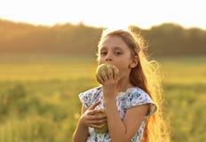 Zabawa dzieciaka piękna dziewczyna z długie włosy joying i gryźć zielenią ap Zdjęcia Stock