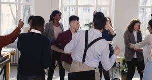 Zabawa Kaukaski korporacyjny kierownik robi niemądremu świętowanie tana spacerowi z grzebak twarzą wraz z biurowymi kolegami zbiory wideo