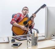 Zabawa męski bezpartyjnik cieszy się bawić się gitarę przy jego komputerowym biurkiem Obrazy Royalty Free