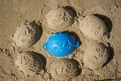 Zabawa piaska twarze chłopiec zdjęcia stock